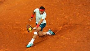 El jugador profesional de tenis Rafa Nadal mantiene su balance mientras devuelve tiros complicados.