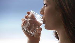 Una mujer bebe un vaso de agua.
