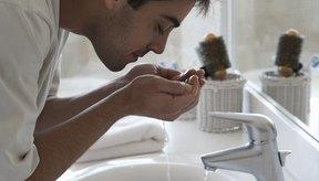 Un hombre lava su rostro en la pileta del baño.
