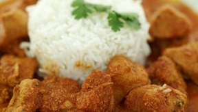 Sirve pollo marinado al curry con arroz integral para una comida abundante y sabrosa.