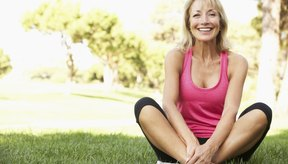 Una mujer sana se sienta en la hierba en el parque.