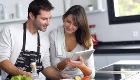 Pareja en la cocina usando una tablet para hacer la cena.