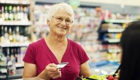 Mujer entregando la tarjeta de crédito en una tienda de comestibles.
