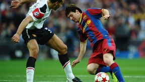 Lionel Messi, del Barcelona, elude al mucho más alto Rio Ferdinand del Manchester United.