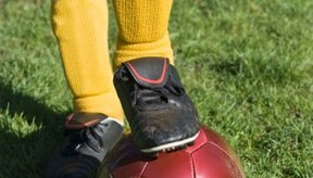 El dolor en la rodilla puede ocurrir mientras se patea un balón de fútbol.