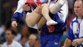 Bela Karolyi lleva a Kerri Strug, lesionada durante las Olimpíadas de 1996.