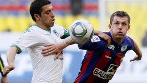 Jugadores de la liga de fútbol ruso intentan empujarse entre sí fuera del camino para conseguir el balón.