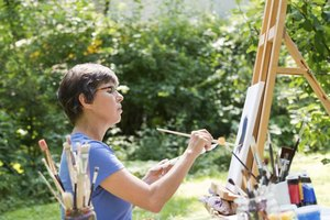 A woman painting at an easel outside in a garden.