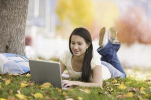 Teenage girl using laptop on grass field.