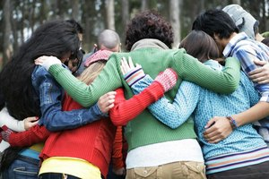 A group of people hugging in a circle outside.