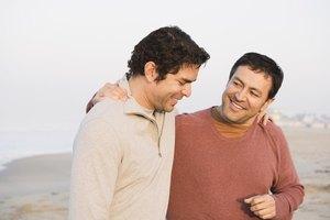 Man hugging his friend on the beach.