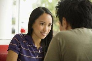 Close-up of boyfriend talking to girlfriend in restaurant