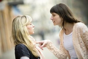 Two women having a tense conversation in the street.