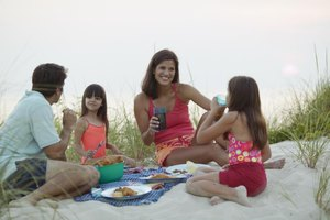A family enjoying a picnic together at the beach.