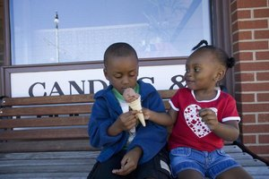 Young boy and girl sharing ice cream.