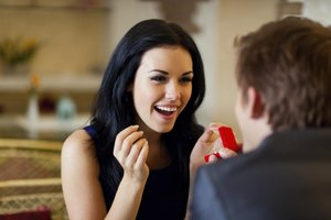 A man presenting a ring to his excited girlfriend.