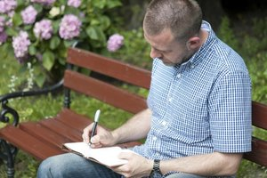 A man writing in a journal on bench in a garden.