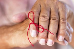 A close-up of an elderly woman's hands with a string tied around her finger.