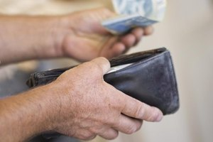 A close-up of a man offering cash from his wallet.