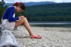 Teen writing a letter while sitting on a log in front of water.