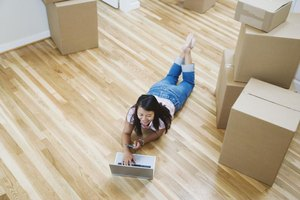 Woman using laptop in new house amongst moving boxes.