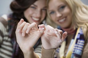 Two young women entwining their pinky fingers together as a sign of friendship.
