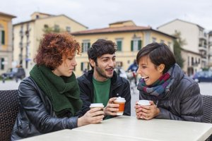 Three people having coffee together at an outdoor table.