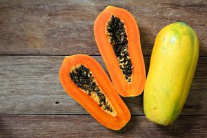 A halved papaya on a wooden table.