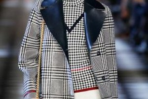 A model walking the runway during a Tommy Hilfiger show displays the brand's preppy chic style.