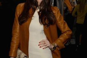 Give your style a boost by pairing a brown leather jacket with a white dress.