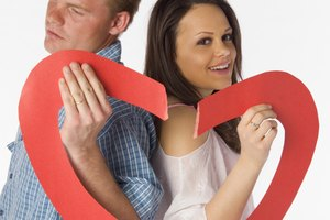 Couple holding two torn parts of a heart