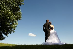 Back view of bride and groom embracing outdoors in park