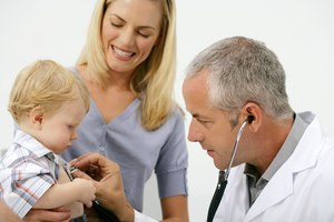 Mother holding baby so doctor can listen to chest with thermometer