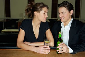 Couple having drinks at bar, smiling