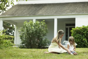 Young woman playing with daughter (4-5) on lawn outside house