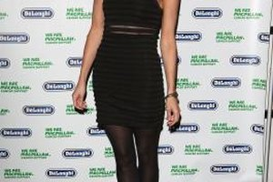 Actress Kara Tointon pairs a sleek black dress with high-heeled ankle boots.