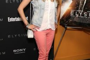 Actress Julianne Michelle wears peach jeans with a white blouse and faded denim vest.