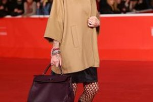 Italian actress Paola Barale complements her outfit with a dark brown purse.