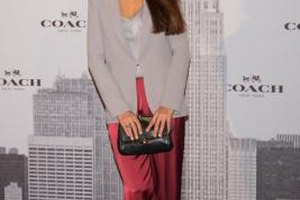 Spanish actress Monica Estarreado wears red satin pants with a gray top and blazer at Madrid's Coach grand opening in 2013.