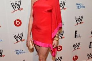 Madison Pard pairs a bright red dress with gold jewelry and a neutral clutch and shoes.