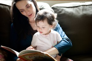 Mother reading to daughter on sofa at home