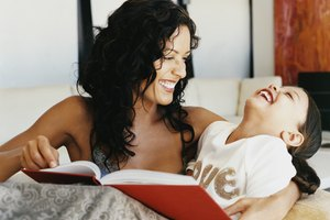Young Girl Laughing as Her Mother Reads a Book to Her