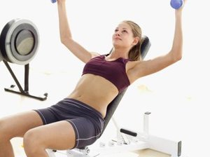 How to Lay on an Incline Bench for a Dumbbell Fly With Both Arms