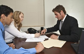 Title officer going over real estate paperwork with couple.