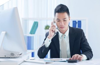 Insurance agent talking on phone in office