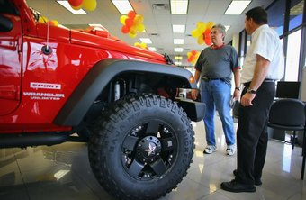 A sales consultant talking to a customer about a new vehicle in a showroom.