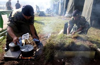 Army chefs prepare a meal outdoors in the field.