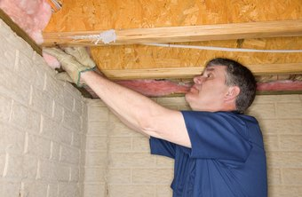 Weatherization workers check for insulation in basement ceilings.