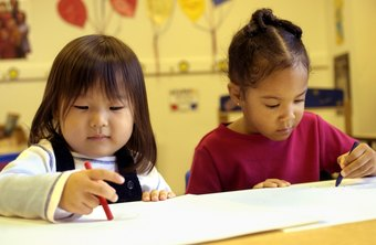 Preschool teachers help students with basic writing skills.