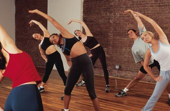 Gym fitness instructors lead clients in group classes.